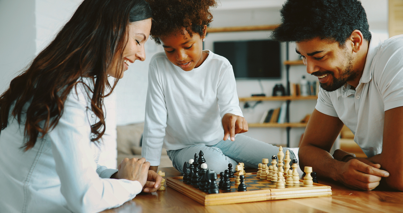 mom and dad playing chess with daughter